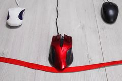 Computer mouse on a white background. Interactive race on speed between the red, white and black computer mouse on a wooden gray background. The input device for Royalty Free Stock Photography