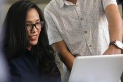 Interaktion und Kommunikation zwischen attraktivem asiatischem weiblichem und männlichem Mitarbeiter lizenzfreie stockbilder