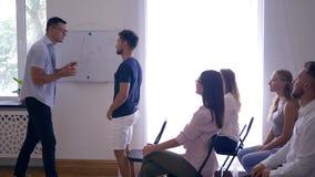 Interaktywny szkolenie na konwersatorium, trener daje prezentaci nowy projekt i słucha koledzy podnosi ręki up wewnątrz zbiory wideo
