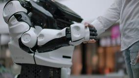 Interazione dell'uomo e tecnologie moderne di intelligenza artificiale Chiuda sulla mano maschio dello scienziato stringe robot video d archivio