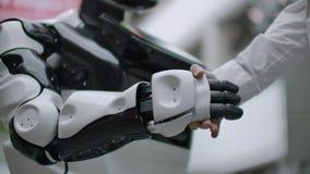 Interazione dell'uomo e tecnologie moderne di intelligenza artificiale Chiuda sulla mano maschio dello scienziato stringe robot archivi video