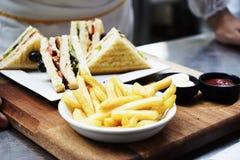Intercala las hamburguesas con la carne, el queso y los verdes en una placa blanca Imagen de archivo