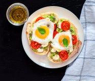 Intercale las tostadas con el agg, los tomates cereza, la mozzarella, el aguacate, la albahaca y el aceite de oliva Opinión super imagenes de archivo