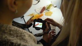 Intercambio de ideas entre bastidores del photoshoot de la fotografía de la comida almacen de metraje de vídeo