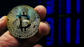Intercambio y comercio de Cryptocurrency Mano que sostiene la moneda del bitcoin BTC almacen de video
