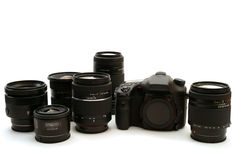 Interchangeable Lens Digital Camera. A view of an advanced interchangeable lens digital camera body with a group of matching lenses Royalty Free Stock Photos