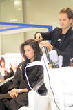 Intercharm XXI International Perfumery and Cosmetics Exhibition Beautiful young brunette woman doing a new stylish haircut Curling Stock Image
