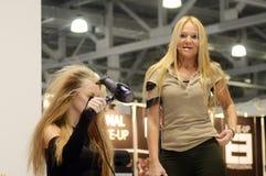 Intercharm XXI Międzynarodowa mydlarnia i kosmetyk wystawa Ćwiczymy fryzjera męskiego Dziewczyny głowa suszy hairdryer Fryzjerstw Fotografia Royalty Free