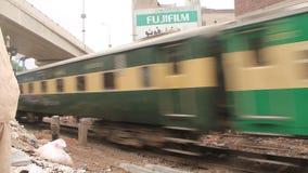 Intercity τραίνο σιδηροδρόμων του Πακιστάν που διασχίζει την πύλη σιδηροδρόμων σε Gujranwala απόθεμα βίντεο