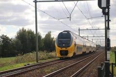 Intercity τραίνο στη διαδρομή σιδηροδρόμου μεταξύ του γκούντα και του Ρότερνταμ σε Moordrecht στοκ φωτογραφία
