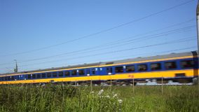Intercity Direct train passing. Dutch Railways Intercity Direct train passing at high speed during a summer day stock video footage