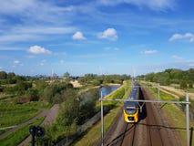 Intercity drev på järnvägsspår med naturkompensations- och vindturbiner producera grön energi royaltyfri foto