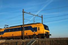 Intercity drev på spår på Nieuwerkerk den aan hålan IJssel i Nederländerna under vinter i aftonsnö arkivbild