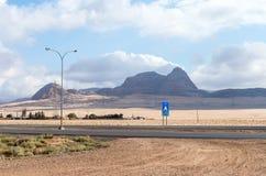 Intercity rutt som passerar nära foten av de röda bergen i söderna av Jordanien, inte långt från den Maan staden arkivfoton