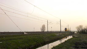 Intercity train passing in a sunset. Intercity train passing on an elevated railroad track in the country side at the end of the day stock video