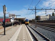 Intercity vänta för dubbel däckare längs plattformen av järnvägsstationgouda i Nederländerna royaltyfri foto