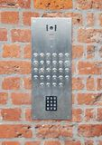 Intercom. Close-up on a intercom doorbell and access code panel on brick wall residential building Stock Image