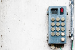 Intercom system. An wired intercom device with round numeric buttons attached to the white rough wall royalty free stock image