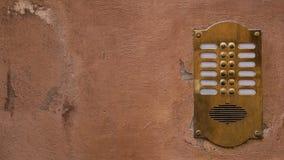 Intercomunicador de bronce viejo en una pared vieja con la pintura de la peladura 16:9 del ratio fotos de archivo