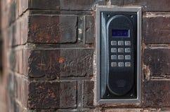 Intercomunicador velho em uma parede de tijolo vermelho Imagem de Stock