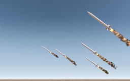 Intercontinental Ballistic Missile. A row of intercontinental ballistic missiles launching in a desert on a blue sky backgrund - 3D render Royalty Free Stock Photography