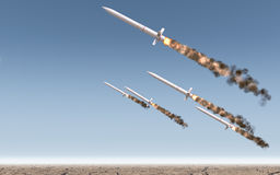 Intercontinental Ballistic Missile. A row of intercontinental ballistic missiles launching in a desert on a blue sky backgrund - 3D render Stock Photography