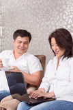 Intercultural couple reading book. Peaceful time. Asian couple reading book at home and drinking tea Stock Photo