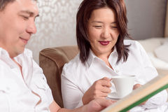 Intercultural couple reading book. Peaceful time. Asian couple reading book at home and drinking tea Royalty Free Stock Photos
