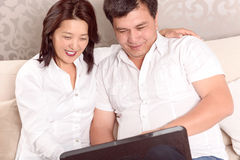Intercultural family discussing new plans. New happy plans.  Asian family sitting home at laptop Stock Image