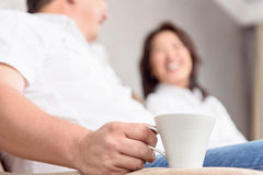Intercultural family drinking coffee. Happy moments. Cople smimiling and drinking tea on sofa at home Stock Photo