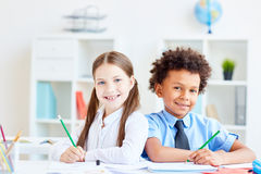 Intercultural friends. Multi-racial schoolchildren with pencils sitting by desk close to one another Royalty Free Stock Image