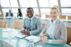 Intercultural partners. Caucasian businesswoman and African businessman looking at camera at conference Royalty Free Stock Photos