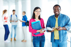 Intercultural students. Cheerful students with books looking at camera Stock Images