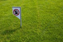 Interdisant le signe vous ne pouvez pas marcher avec un chien sur la pelouse verte Marche d'aucun animal images libres de droits