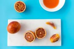 Intere, arance sanguinelle divise in due e schiacciate sul blu Immagine Stock