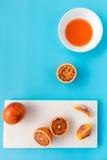 Intere, arance sanguinelle divise in due e schiacciate sul blu Immagini Stock