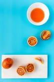 Intere, arance sanguinelle divise in due e schiacciate sul blu Fotografia Stock Libera da Diritti