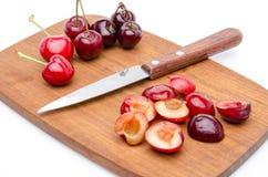 Intere e ciliege snocciolate con un coltello su un tagliere di legno Fotografie Stock