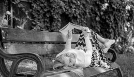 Interessant boek Slim en mooi Het slimme dame ontspannen Meisjeslezing in openlucht terwijl het ontspannen op bank Het meisje leg stock afbeeldingen