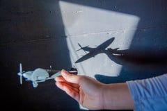 Interessante abstracte achtergrond met een schaduw op de concrete muur van de zonneblinden Een hand houdt een vliegtuig en er zij stock afbeeldingen