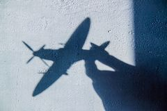 Interessante abstracte achtergrond met een schaduw op de concrete muur van de zonneblinden Een hand houdt een vliegtuig en er zij royalty-vrije stock fotografie