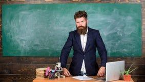 Interessanter Gesprächspartner des Lehrers als Berechtigung Charismatischer Hippie-Stand des Lehrers nahe Tabellenklassenzimmerta lizenzfreie stockbilder