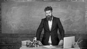 Interessanter Gesprächspartner des Lehrers als Berechtigung Charismatischer Hippie-Stand des Lehrers nahe Tabellenklassenzimmerta stockfotografie