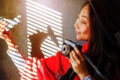 Interessanter Hintergrund für Reise Das Mädchen hält die Fläche und die Kamera steht nahe der Wand und dem Lächeln stockfotos