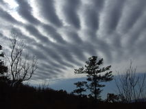Interessantes lineares Wolkenmuster mit Bergen Stockbilder