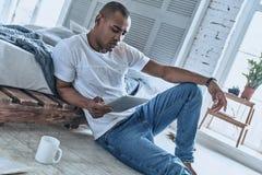 interessar Homem africano novo considerável que usa a tabuleta digital w fotos de stock