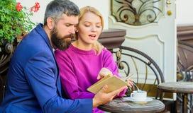 Interesses comuns Homem com barba e mulher loura na data romântica Os pares no amor sentam o terraço do café Tâmara romântica foto de stock