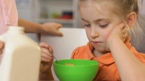Interessierende auslaufende Milch des älteren Bruders in der Schüssel mit Getreide für Schwester, Frühstück stock video