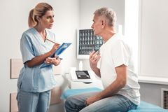 Interessierende blauäugige Krankenschwester, die aufmerksam auf Patienten hört lizenzfreie stockfotos