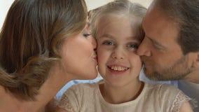 Interessierende Eltern, die zart auf Backen ihre wenig Tochter, Liebe und Stolz küssen stock footage